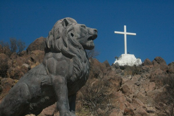 Bronze lion solar symbol below cross solar symbol next to San Xavier del bac Mission
