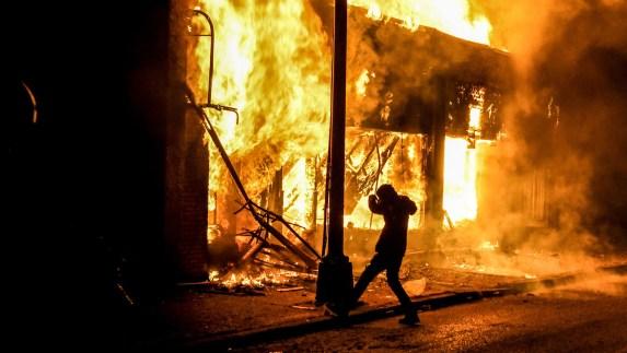 Un manifestante rodeado de fuego en Minneapolis, Minnesota (Chandan KHANNA / AFP)