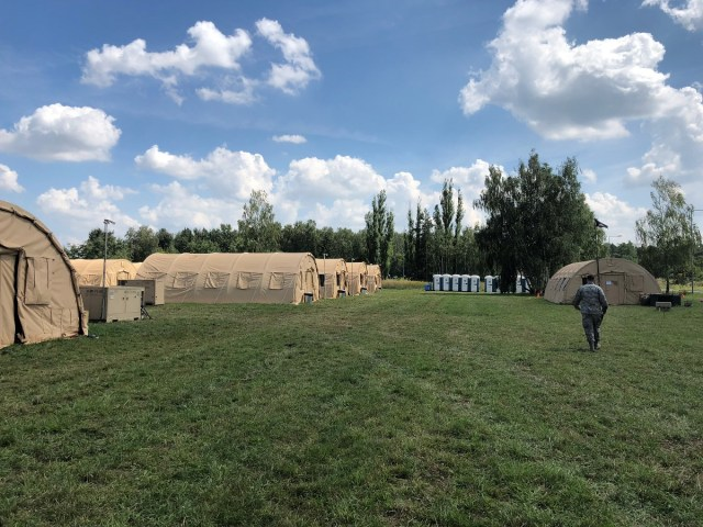 The first-ever DABS proof of concept officially kicked off July 16, when vehicles and supplies started arriving at Poland's 31st Air Base. This photo shows 12 tents used for living quarters, left, with the headquarters of the 1st Combat Communications Squadron, which provided classified and unclassified radio and internet, right. (Valerie Insinna/Staff)