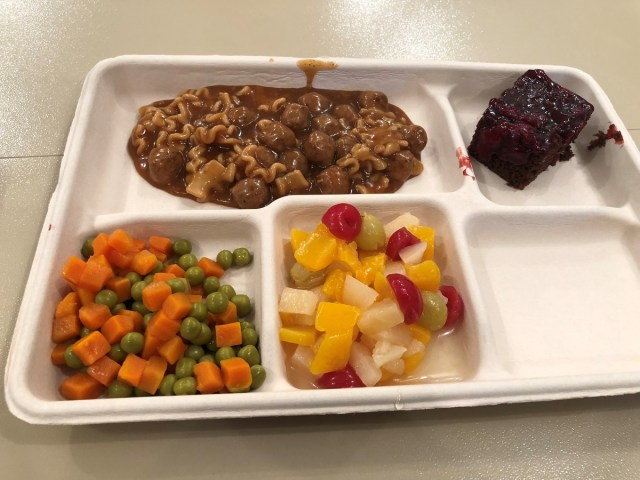 A typical hot lunch of noodles and gravy, fruit cocktail, vegetables, and chocolate cake. The meals were prepared and served by airmen from the 200th RED HORSE Squadron DET 1, Ohio Air National Guard. (Valerie Insinna/Staff)