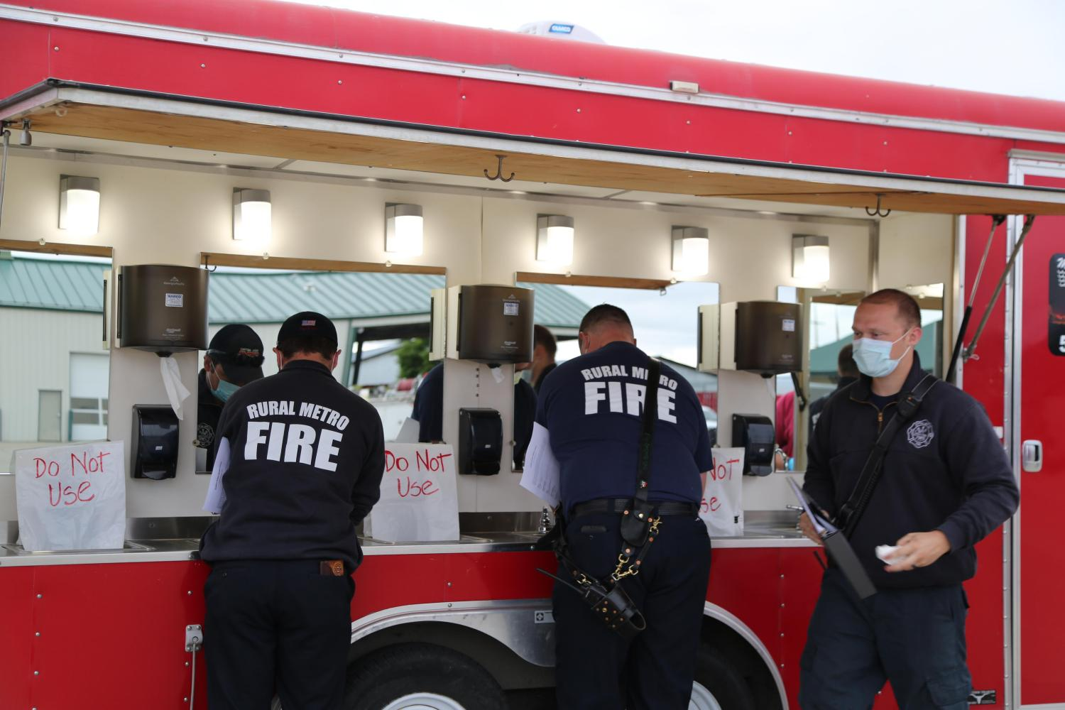 Firefighters use a hand-washing station with socially distanced sinks at a training event in June, 2020.