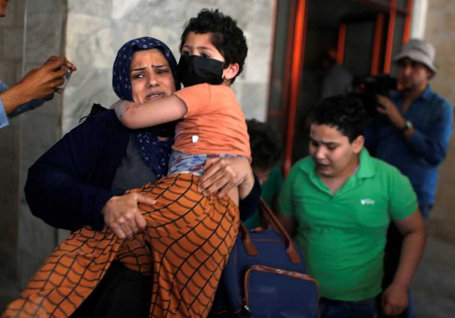Palestinians evacuate following an Israeli air strike on a building, amid a flare-up of Israeli-Palestinian violence, in Gaza City May 11, 2021. REUTERS/Mohammed Salem