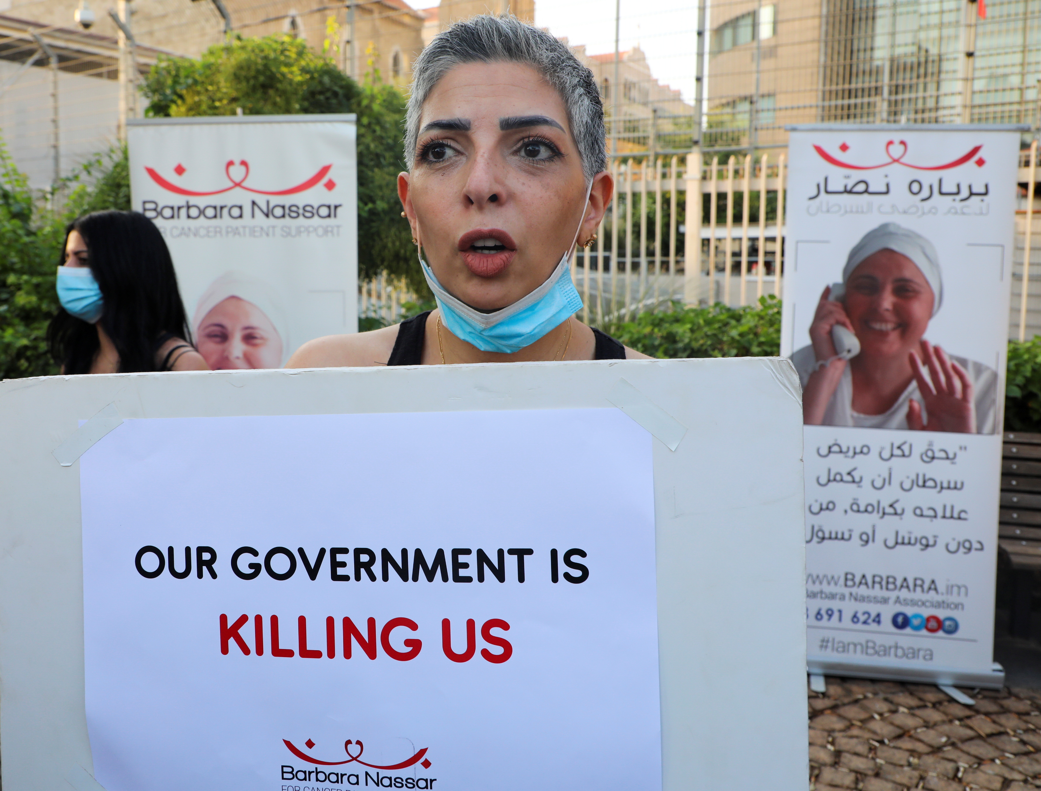 A cancer patient holds a sign, during a sit-in demonstration as shortages of cancer medications spread, in front of the U.N. headquarters in Beirut, Lebanon August 26, 2021. Picture taken August 26, 2021. REUTERS/Mohamed Azakir