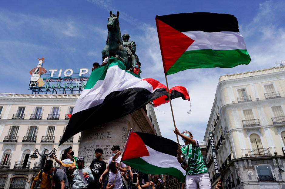 People hold flags during a protest in support of Palestinians amid their ongoing conflict with Israel, at King Carlos III statue, in Madrid, Spain May 15, 2021. REUTERS/Juan Medina