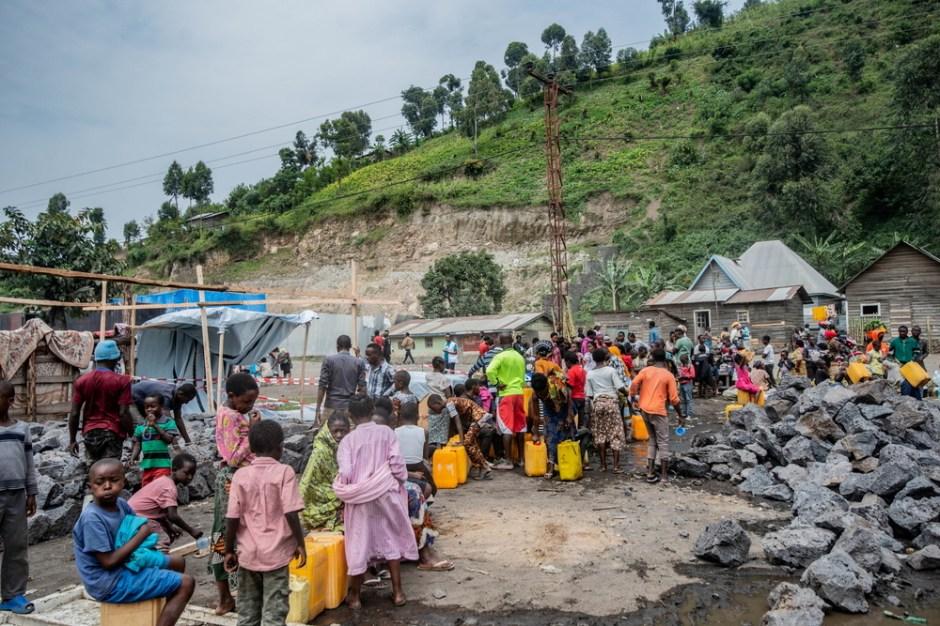 Los civiles congoleños desplazados que fueron evacuados de los temblores de tierra recurrentes como réplicas después de que las casas se cubrieron con la lava depositada por la erupción del monte Nyiragongo, reciben agua en un punto de distribución por miembros del equipo de Médicos Sin Fronteras (MSF) cerca de su campamento temporal en Sake, República Democrática de Congo 28 de mayo de 2021. Fotografía tomada el 28 de mayo de 2021. Médicos sin fronteras / Folleto a través de REUTERS / Foto de archivo