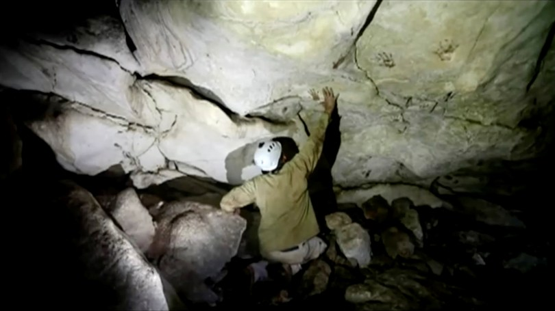Archeologist Sergio Grosjean explores a cave with hand prints, reportedly 1,200 years old, in Merida, Mexico April 2021, in this screengrab taken from a handout video. SERGIO GROSJEAN/Handout via REUTERS