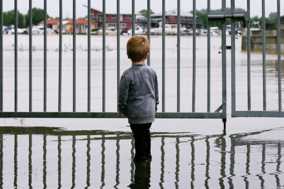 A child looks on as water floods through a fence in Wessem, Netherlands, July 16, 2021. REUTERS/Eva Plevier/File Photo
