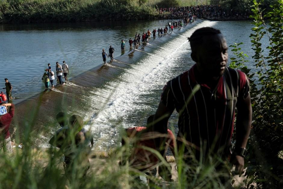 Migrantes que buscan asilo en los EE. UU. Caminan en el río Grande cerca del Puente Internacional entre México y EE. UU., Mientras esperan ser procesados, en Ciudad Acuña, México, el 16 de septiembre de 2021. Según las autoridades, algunos migrantes cruzan de un lado a otro a México para comprar alimentos y suministros.  REUTERS / Go Nakamura