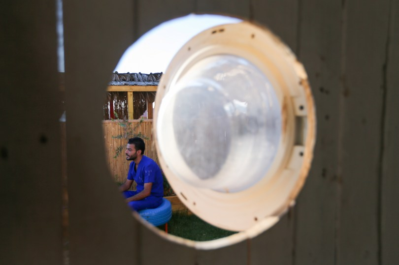 Palestinian artist, Ali Mhana, is seen through a glass door of a washing machine that he used as a window of a his makeshift office at an environment-friendly beachfront cafe in Gaza July 8, 2021. Picture taken July 8, 2021. REUTERS/Ibraheem Abu Mustafa
