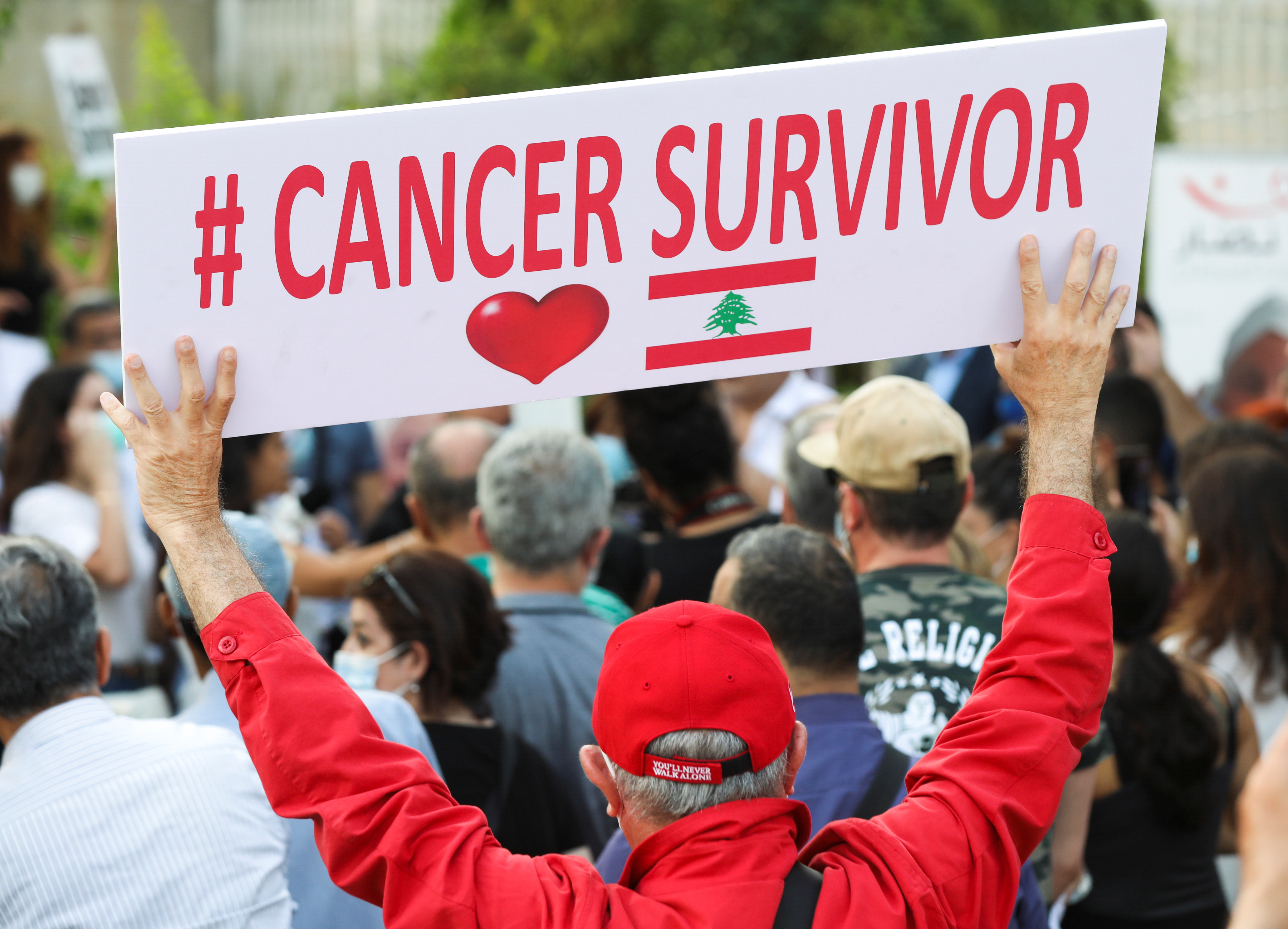 A man holds a sign during a sit-in demonstration as shortages of cancer medications spread, in front of the U.N. headquarters in Beirut, Lebanon August 26, 2021. Picture taken August 26, 2021. REUTERS/Mohamed Azakir