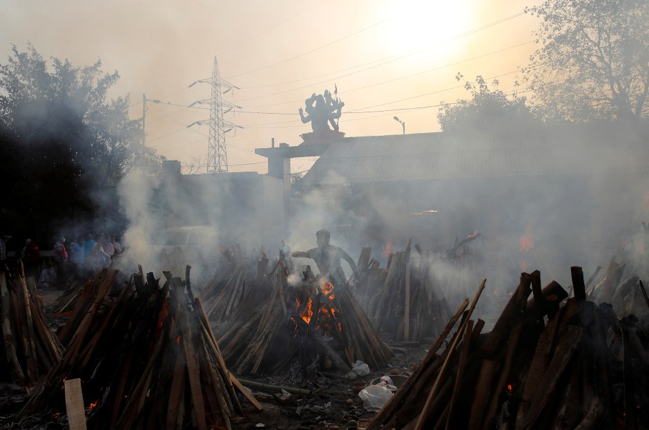 A man performs last rites next to the funeral pyres of those who died from the coronavirus disease (COVID-19), during a mass cremation at a crematorium in New Delhi, India May 1, 2021. REUTERS/Adnan Abidi