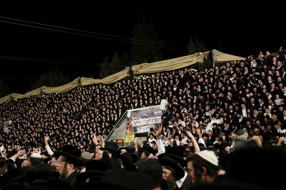 Jewish worshippers sing and dance as they stand on tribunes at the Lag B'Omer event in Mount Meron, northern Israel, April 29, 2021. REUTERS/ Stringer