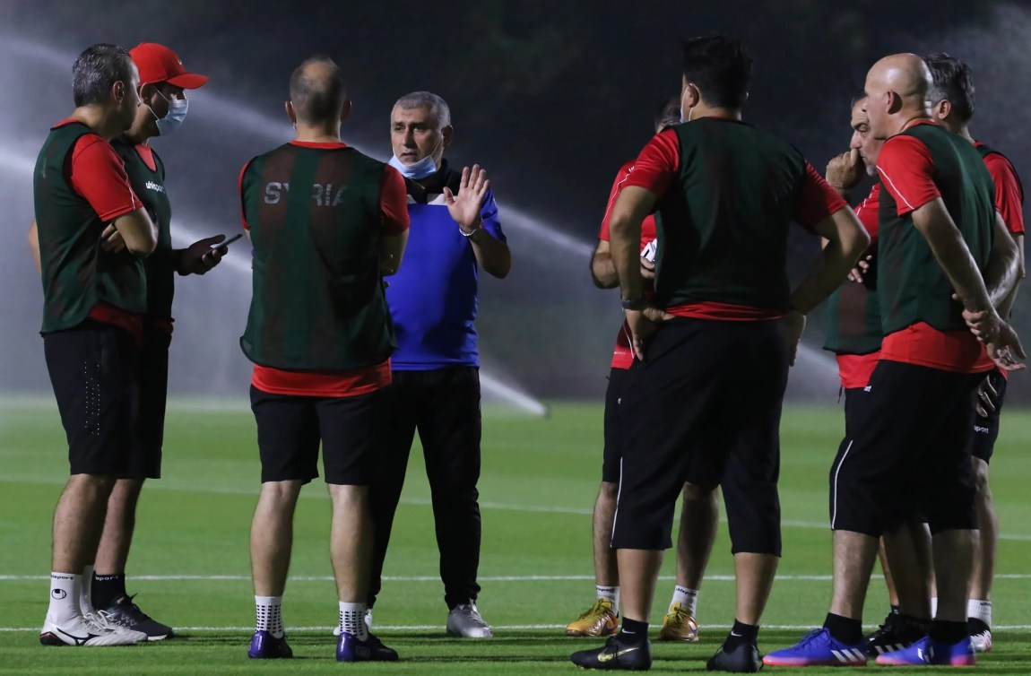 Syria coach Nizar Mahrous talks with his assistants during a training session
