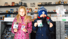 A group of 2 children holding up a pack of hockey cards for National Hockey Card Day 2019