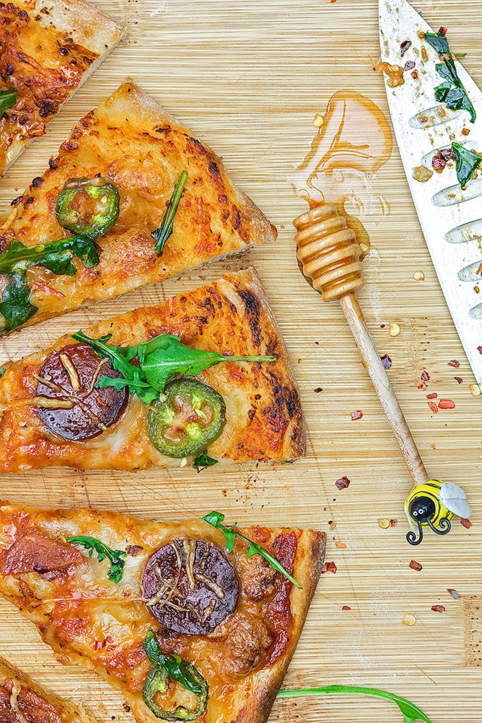 A simple, yet effortlessly stunning pepperoni pizza covered with handfuls of fresh arugula and drizzled with ribbons of chili-spiced hot honey.