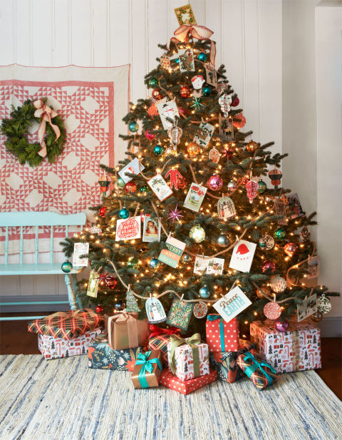 """Overflowing with good tidings, this """"friends and family"""" tree features an assortment of holiday greeting cards (clipped to jute rope with mini clothespins) and a spirited mix of jewel-toned ornaments from the '50s and '60s."""