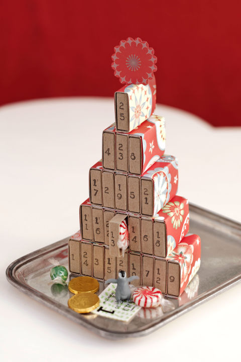 Use ordinary grocery-store matchboxes to count down the days till Christmas. Just hot-glue the tops of empty boxes to one another to form rows (start with nine boxes for the base, and decrease by two until you have a single box). Cut wrapping paper to cover each section; secure with hot glue. Next, hot-glue the rows in a pyramid shape as shown. Use number stamps (available at craft stores) to mark the boxes 1 through 25, then fill with candy and trinkets.