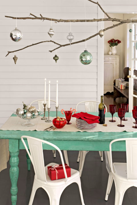 Branch out from conventional tablescapes by using an extra-long tree limb as a platform for displaying ornaments. Simply knot lengths of twine around the branch and hang it from a row of five or six ceiling hooks.