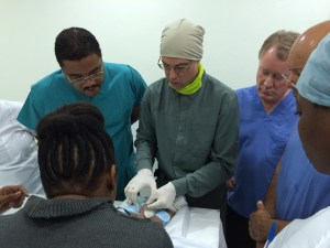 Dr Pollock (centre) provides instruction during a surgical training mission to Rwanda. This year he will take part in a similar mission to Haiti.