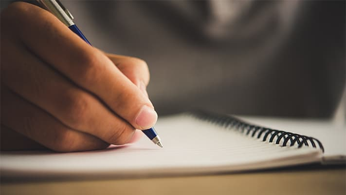 paper pad on a table with a hand on it holding a pen
