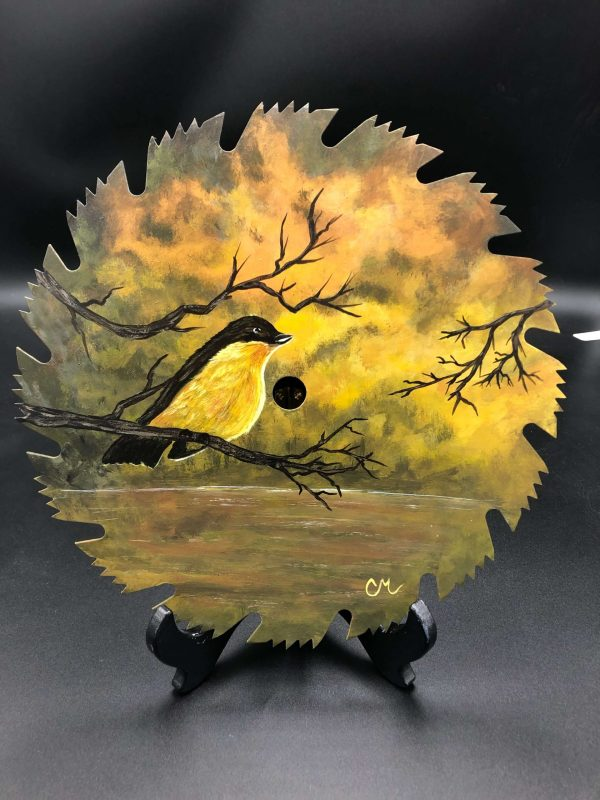 """Morning-Glow—10""""-Acrylic-Painted-Saw-Blade-of-a-yellow-bird-sitting-upon-a-branch-over-water-reflecting-the-yellow-sky"""