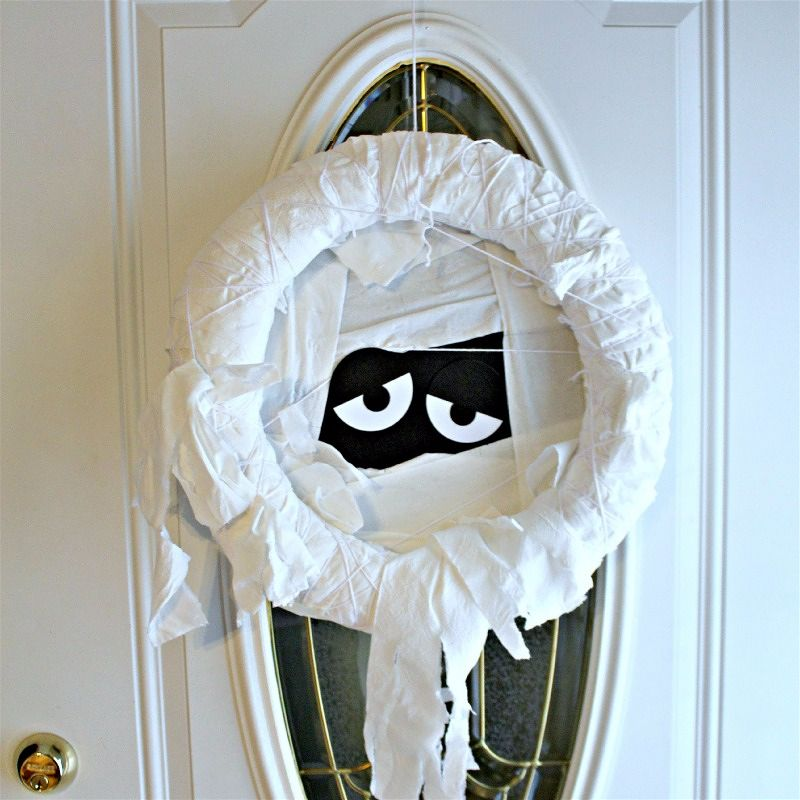 Use toilet paper, paper, and yarn to make your own DIY Toilet Paper Mummy wreath!