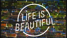 """A neon sign against a brick wall. The sign reads """"LIFE IS BEAUTIFUL"""" in all capital letters."""