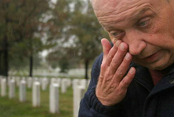 FIRST PLACE: Evan Falk, Ithaca College (Michael Serino, adviser) — Dennis Sendziol, of Naperville, Illinois, visits the gravesite of Sergeant Robert Potock in Arlington National Cemetery on Friday, Oct. 26, 2007. Sendziol owes his life to Potocki after being rescued by him during the Vietnam War.