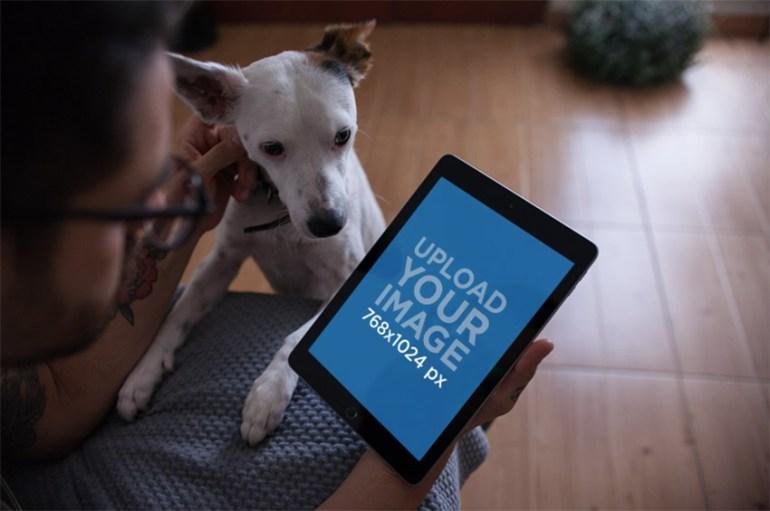 iPad Mockup Featuring a Man Petting His Dog at Home