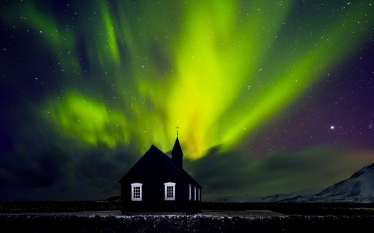 Northern lights behind a sihlouetted church