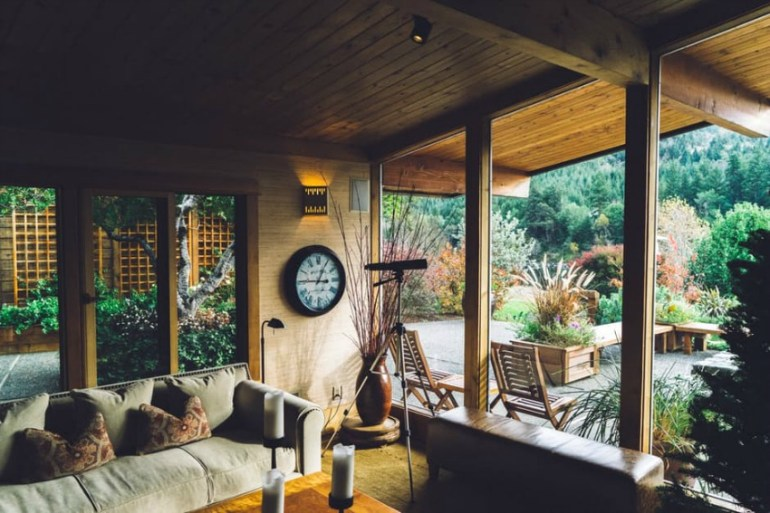 Image is of a living room inside a cottage overlooking the backyard Photo by Unsplash