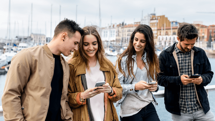 A group of young people looking at their phones and hanging out