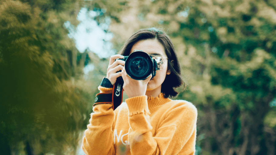 A woman holding a camera up to her face, using her free time in Russian for photography