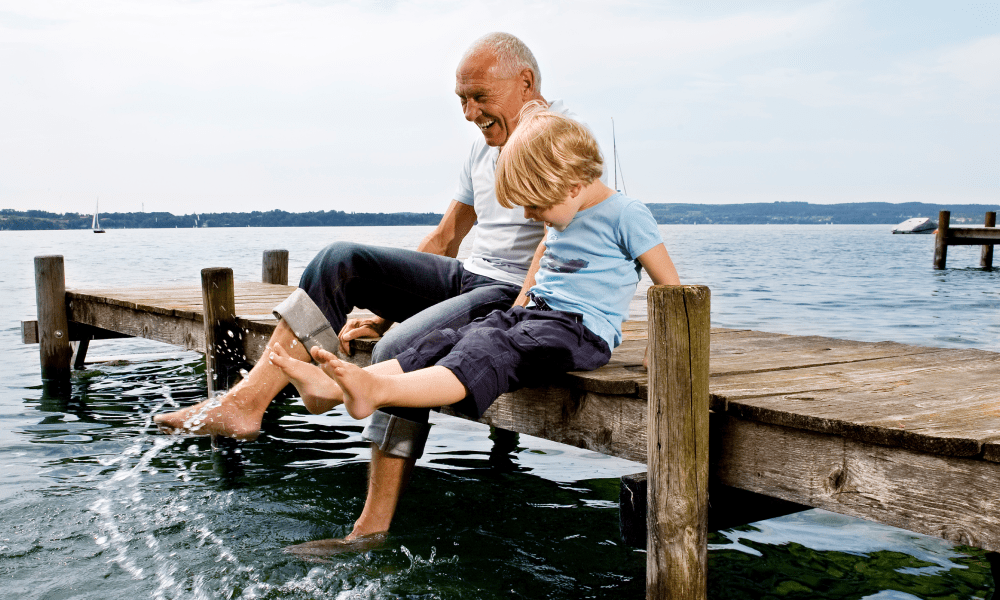 Father and son playing with water, splashing around on a dock