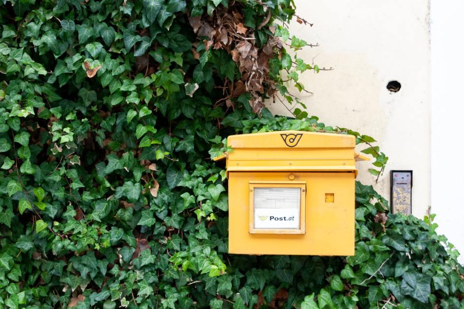 Gelber Briefkasten mit grünen Büschen dahinter