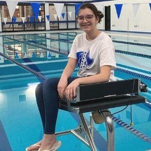 Student posing next to pool
