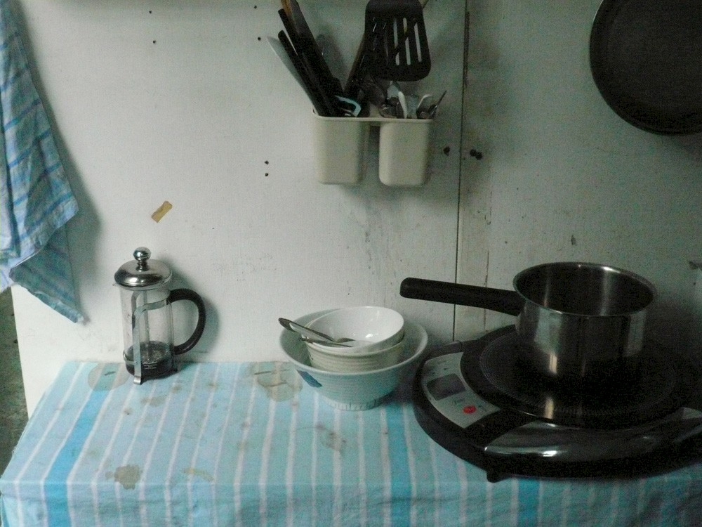 <p>A table covered in a dirty blue tablecloth with bowls, a hot plate, a pot, and a tea strainer on it.</p>
