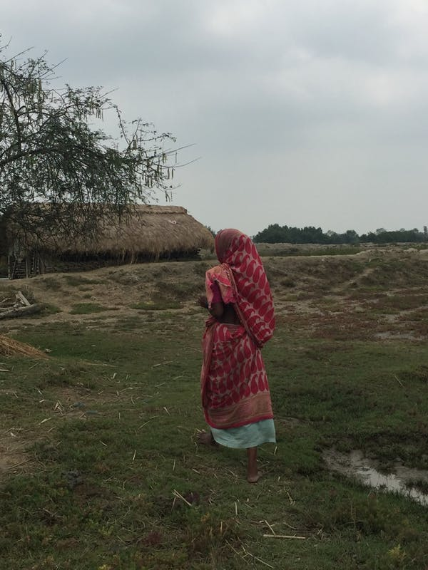 A research participant walking towards her house in West Bengal.