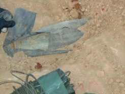 """Center, top: An uncovered artillery projectile enhanced IED - buried, protected with an inner tube. The bottom, center: A Clay custom, C4 based """"Fuck You"""" charge."""