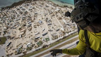 Air Force pararescueman aboard an HH-60G Pave Hawk surveys damage caused by Hurricane Irma