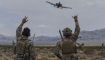 Joint terminal attack controllers wave at an A-10 Thunderbolt II attack aircraft during a show of force on the Nevada Test and Training Range