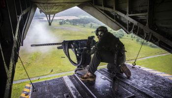Marine Corps crew chief fires an M2 50-caliber machine gun from the back of a CH-53E Super Stallion helicopter