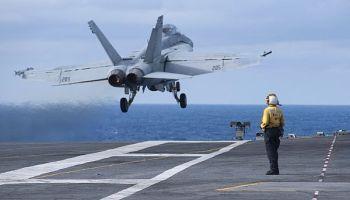 Aviation Boatswain's Mate (Handling) 3rd Class Katie Brown observes an F/A-18F Super Hornet