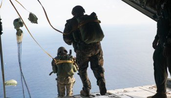IE SHIMA, OKINAWA, Japan — Marines static line jump out of a KC-130J Super Hercules aircraft Nov. 20, 2014 over Ie Shima Training Facility, off the northwest coast of Okinawa, Japan. While performing a low level static line jump, the jumper is released from the aircraft at a low altitude and their chute is pulled open by the aircraft as they exit. The Marines did their static line jumps from an altitude of 1,500 feet for this training. The Marines are with 3rd Reconnaissance Battalion, 3rd Marine Division, III Marine Expeditionary Force. (U.S. Marine Corps photo by Cpl. Drew Tech/Released)