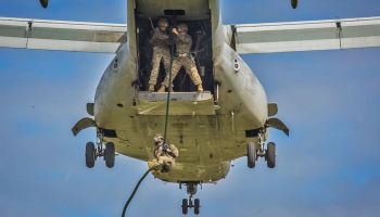 Marine descends from an MV-22B Osprey during training at Camp Hansen, Okinawa, Japan