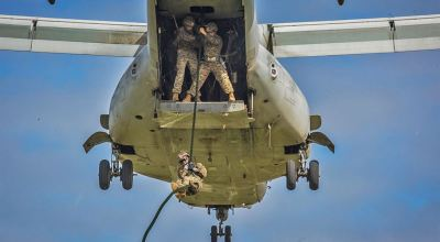 Marine descends from MV-22B Osprey during training at Camp Hansen
