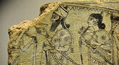 Detail of a glazed terracotta tile from Nimrud, Iraq. The Assyrian king, below a parasol, is surrounded by guards and attendants. 875-850 BC. | The British Museum