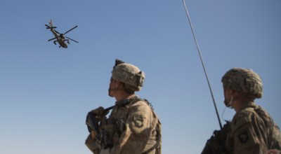 This June 10, 2017 photo released by the U.S. Marine Corpsshows an AH-64 Apache attack helicopter provides security from above while CH-47 Chinooks drop off supplies to U.S. Soldiers with Task Force Iron at Bost Airfield, Afghanistan. | U.S. Marine Corps photo by Sgt. Justin T. Updegraff, Operation Resolute Support via AP