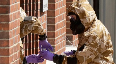 FILE - In this Friday, July 6, 2018 file photo specialist team members in military protective suits use a jar in the front doorway as they search the fenced off John Baker House for homeless people on Rollestone Street in Salisbury, England. Salisbury is where British authorities say the nerve agent Novichok was used against former Russian spy Sergei Skripal and his daughter, Yulia. Both were hospitalized for weeks but eventually recovered. | AP Photo/Matt Dunham, File