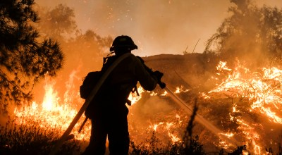 A firefighter battles the Holy Fire burning in the Cleveland National Forest along a hillside at Temescal Valley in Corona, Calif., Thursday, Aug. 9, 2018. Firefighters fought a desperate battle to stop the Holy Fire from reaching homes as the blaze surged through the Cleveland National Forest above the city of Lake Elsinore and its surrounding communities. | AP Photo/Ringo H.W. Chiu